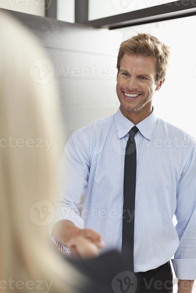 lächelnde Geschäftsleute, die Hände schütteln foto