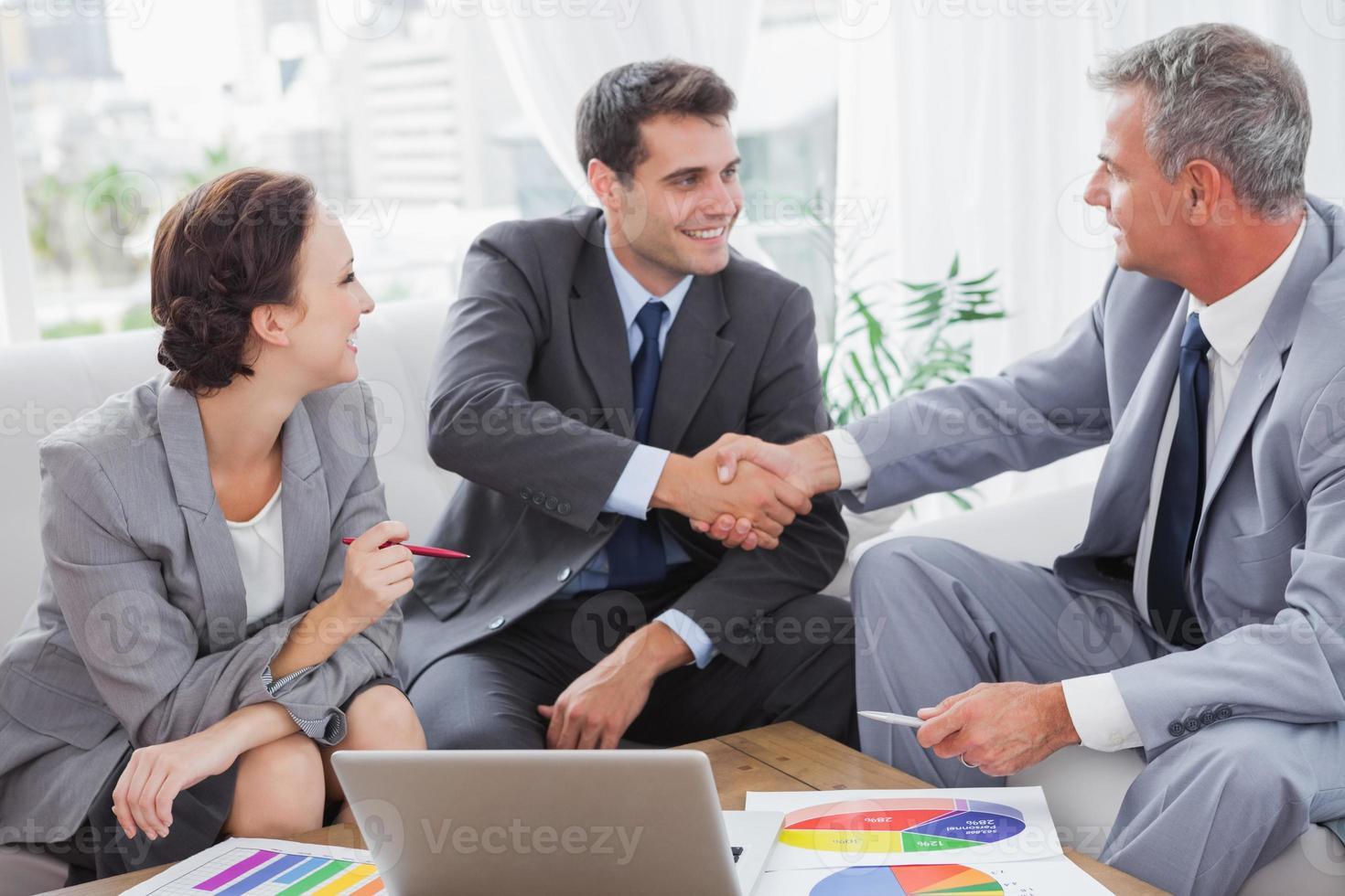 fröhliche Geschäftsleute, die sich auf einen Vertrag einigen foto