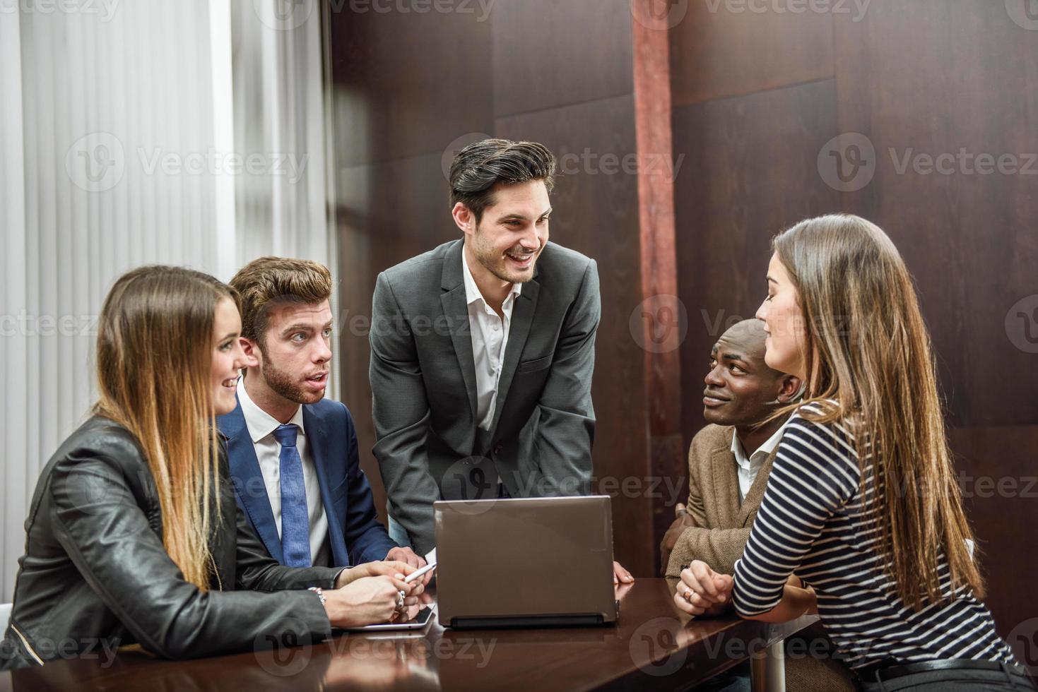 Gruppe von multiethnisch beschäftigten Menschen, die in einem Büro arbeiten foto