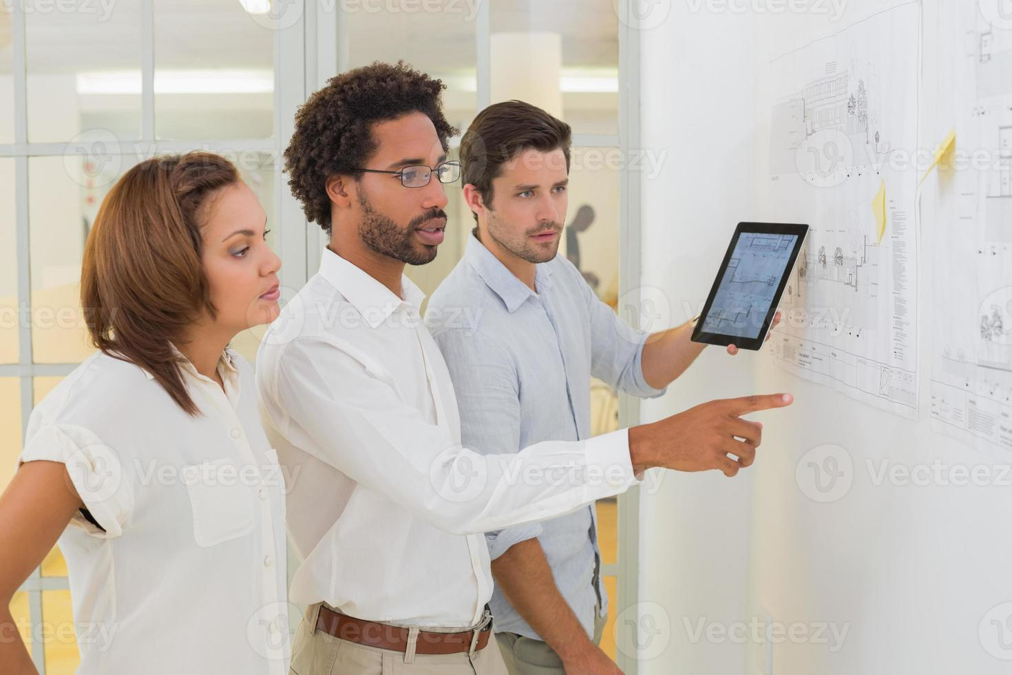 Geschäftsleute, die digitales Tablet beim Treffen im Büro verwenden foto