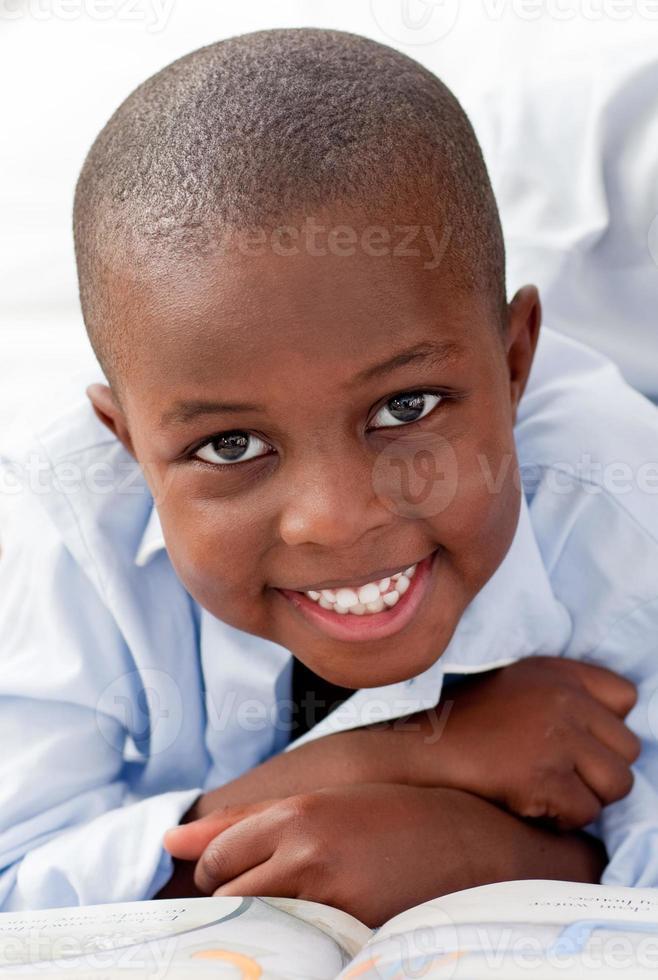 Junge, der lächelnd auf seinem Bett liegt foto