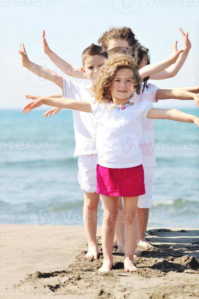 glückliche Kindergruppe, die am Strand spielt foto