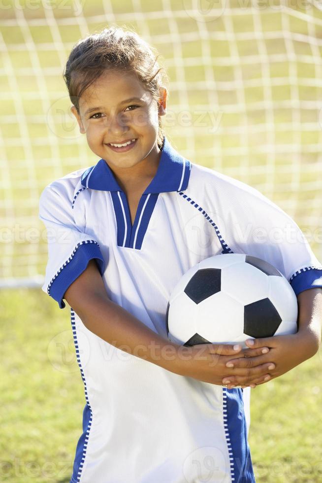 junges Mädchen gekleidet in Fußballausrüstung, die durch Tor steht foto