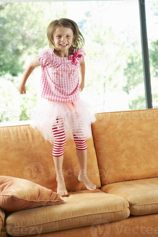 junges Mädchen, das Spaß auf Sofa hat foto