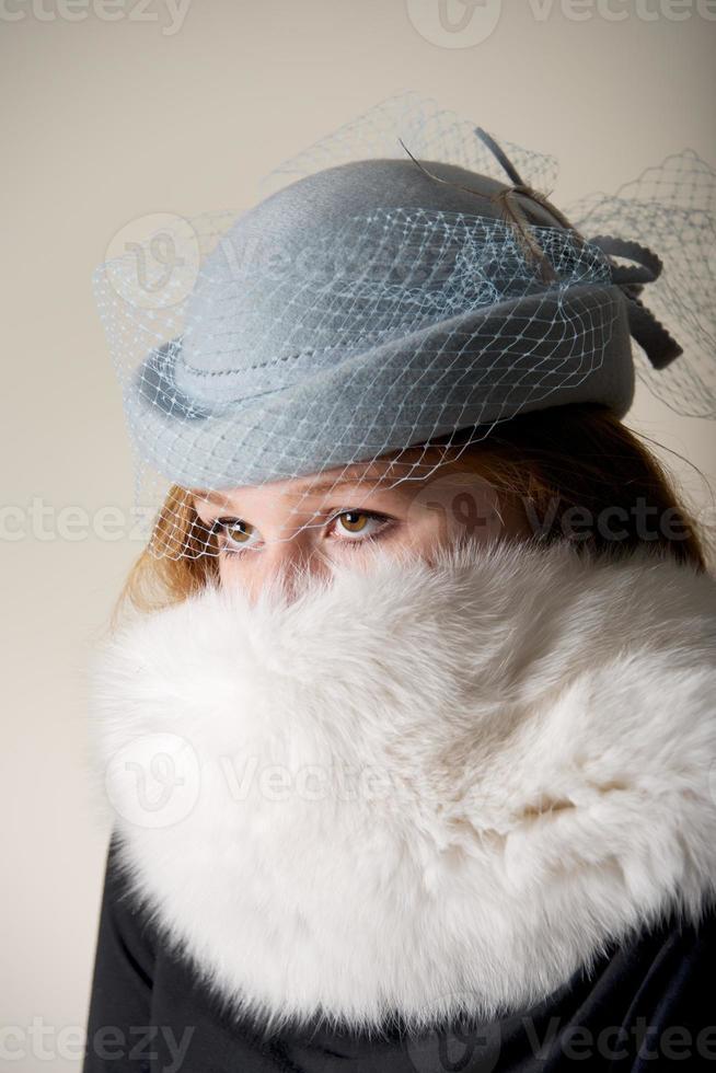 Rothaarige starrt in blau verschleierten Hut und Fell foto
