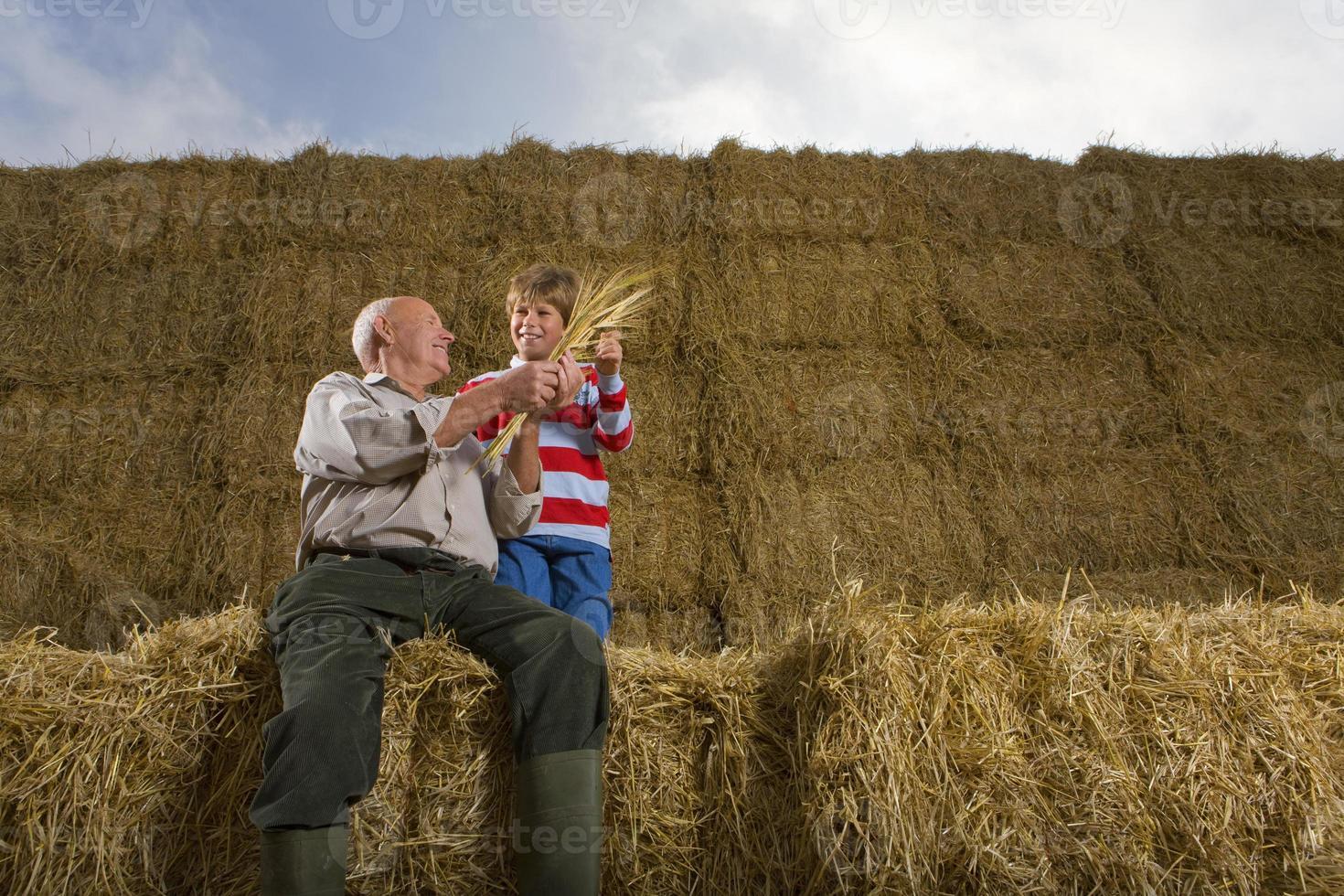 Bauer und Enkel sitzen auf einem Stapel Heuballen foto