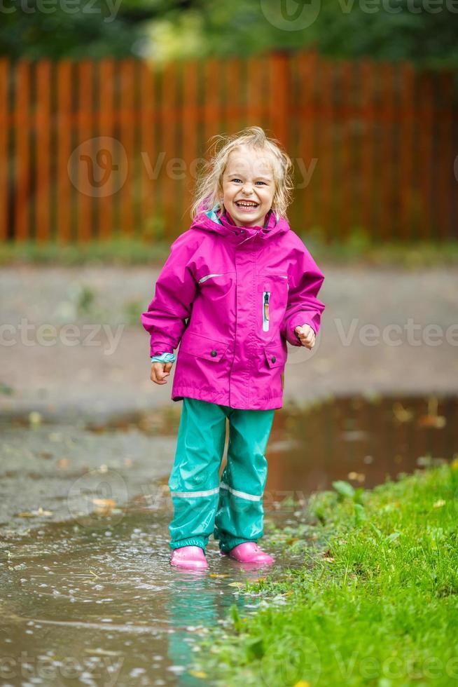 glückliches kleines Mädchen spielt in einer Pfütze foto