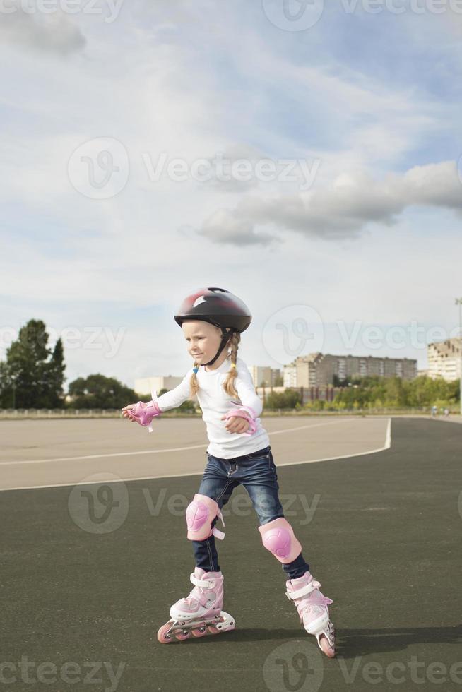 schönes Porträt des kleinen kleinen kaukasischen Mädchens, das Schlittschuh läuft foto