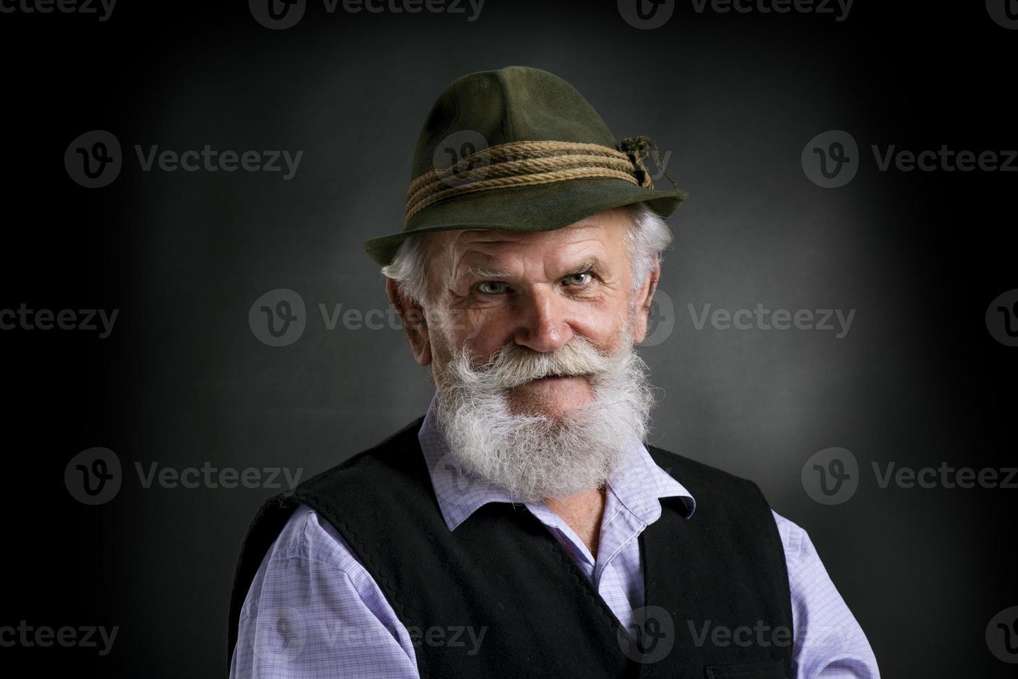 alter bayerischer Mann im Hut auf schwarzem Hintergrund foto