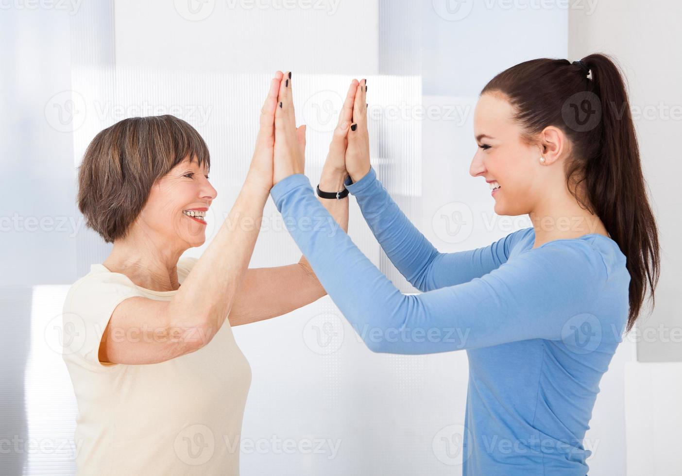 Betreuerin und ältere Frau geben High Five foto