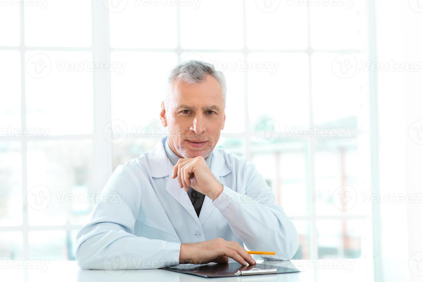 gealterter Arzt im Krankenhausbüro foto