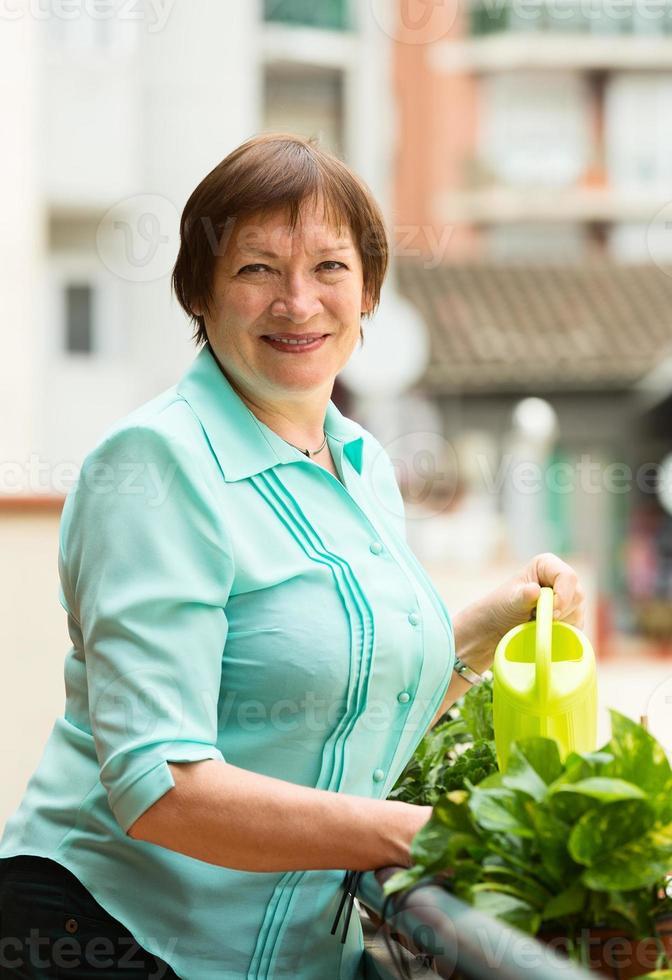 Porträt der älteren Frau, die Hauspflanzen gießt foto