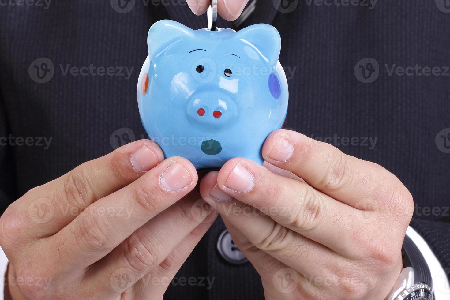 Geschäftsmann, der Sparschweinoffizier hält, legte Geld hinein foto