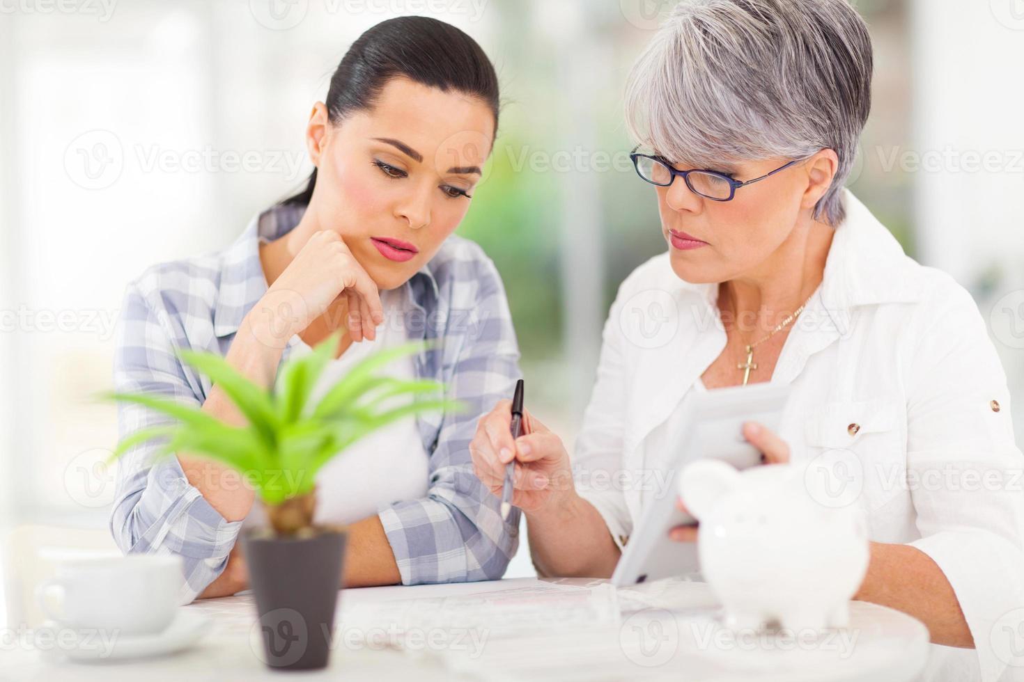 Mutter mittleren Alters hilft Tochter mit ihren finanziellen foto