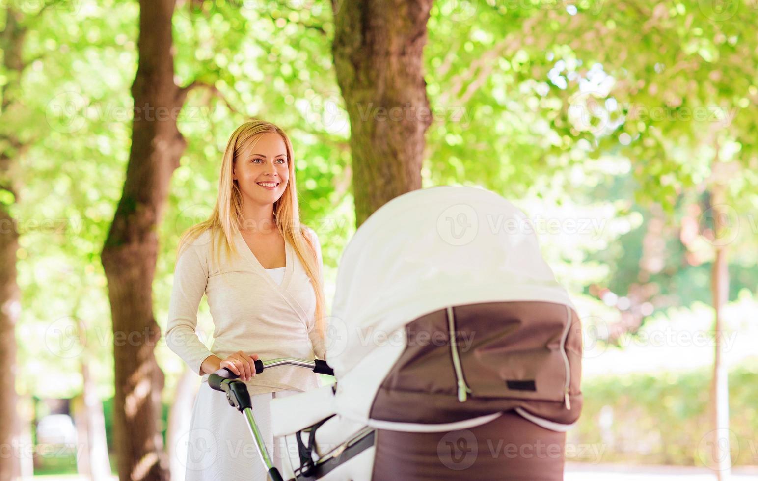 glückliche Mutter mit Kinderwagen im Park foto