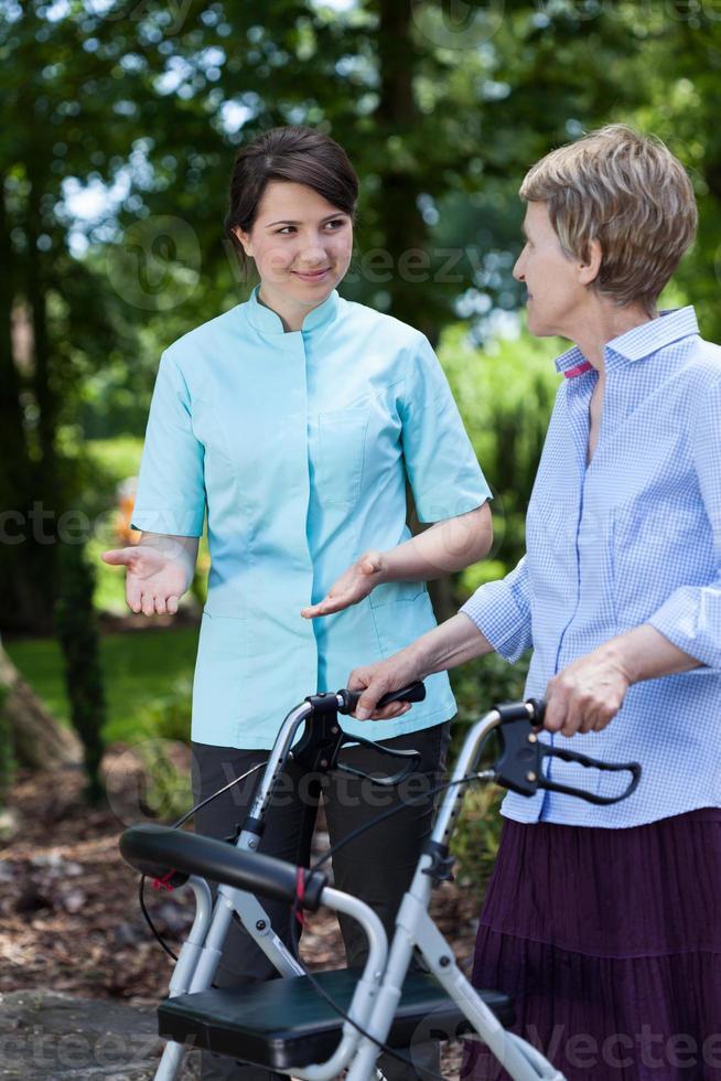 Krankenschwester ermutigt ältere Frau zum Gehen foto