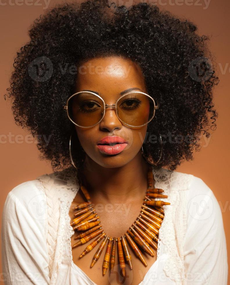 Retro 70er Jahre Mode schwarze Frau mit Sonnenbrille und weißem Hemd. foto