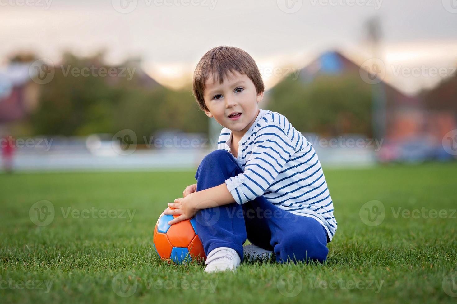kleiner Kleinkindjunge, der Fußball und Fußball spielt und Spaß übertrifft foto
