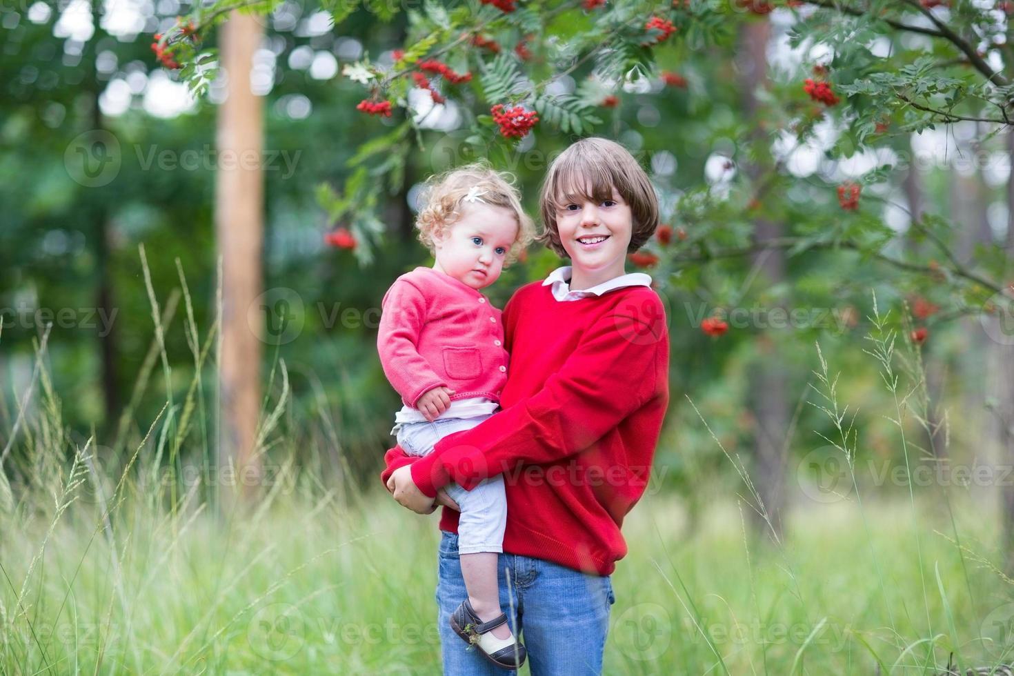 süßer Junge, der seine kleine Schwester hält, die im Herbstpark spielt foto