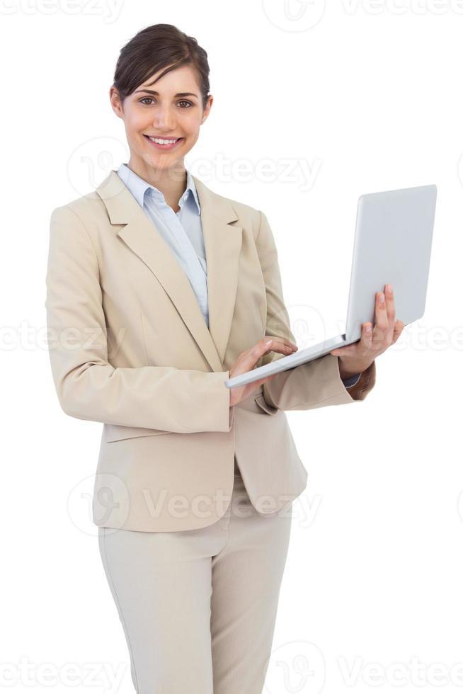 lächelnde junge Geschäftsfrau, die Laptop hält foto