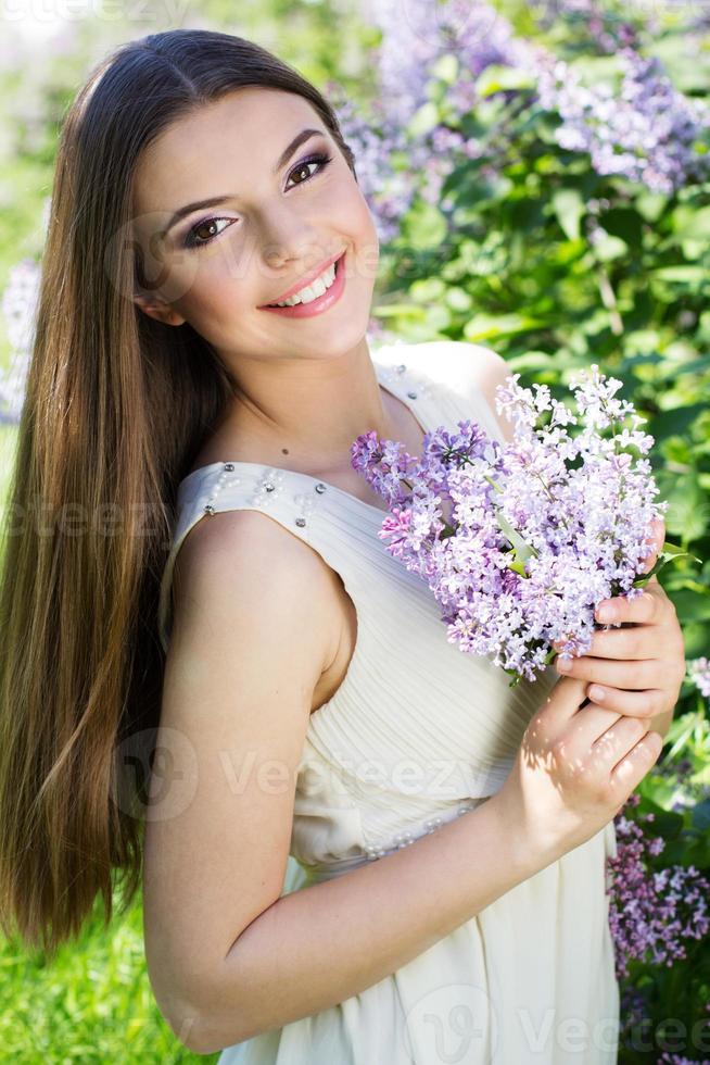 schönes Mädchen mit einer lila Blumen foto