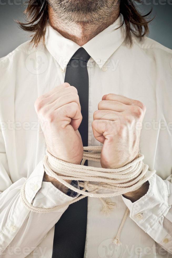 Geschäftsmann mit in Seilen gebundenen Händen foto