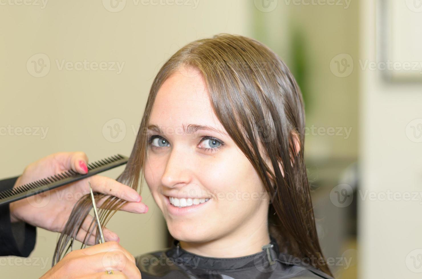 attraktives Mädchen in einem Salon, der in die Kamera lächelt foto