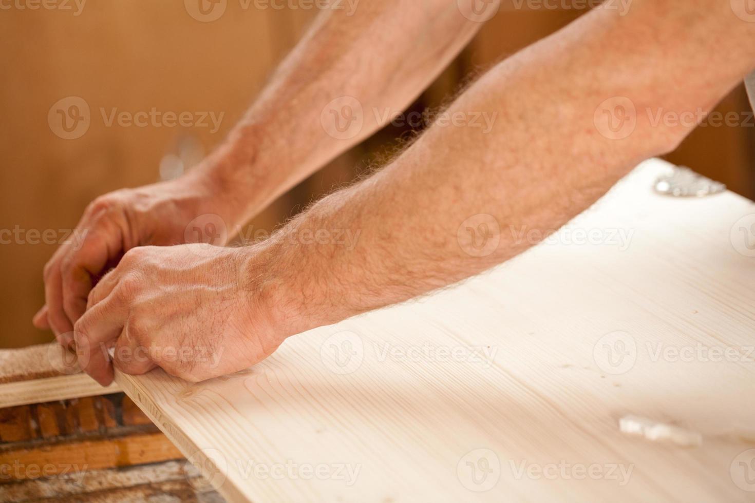Männerhand arbeitet an Holz foto