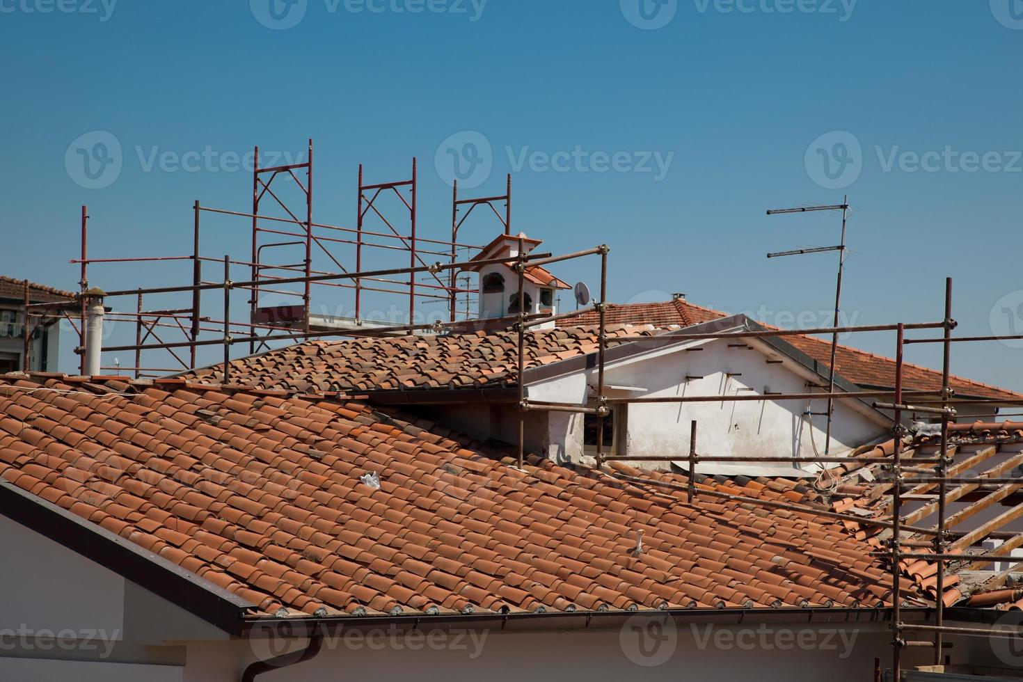 Gerüst und das kaputte Dach eines Hauses foto