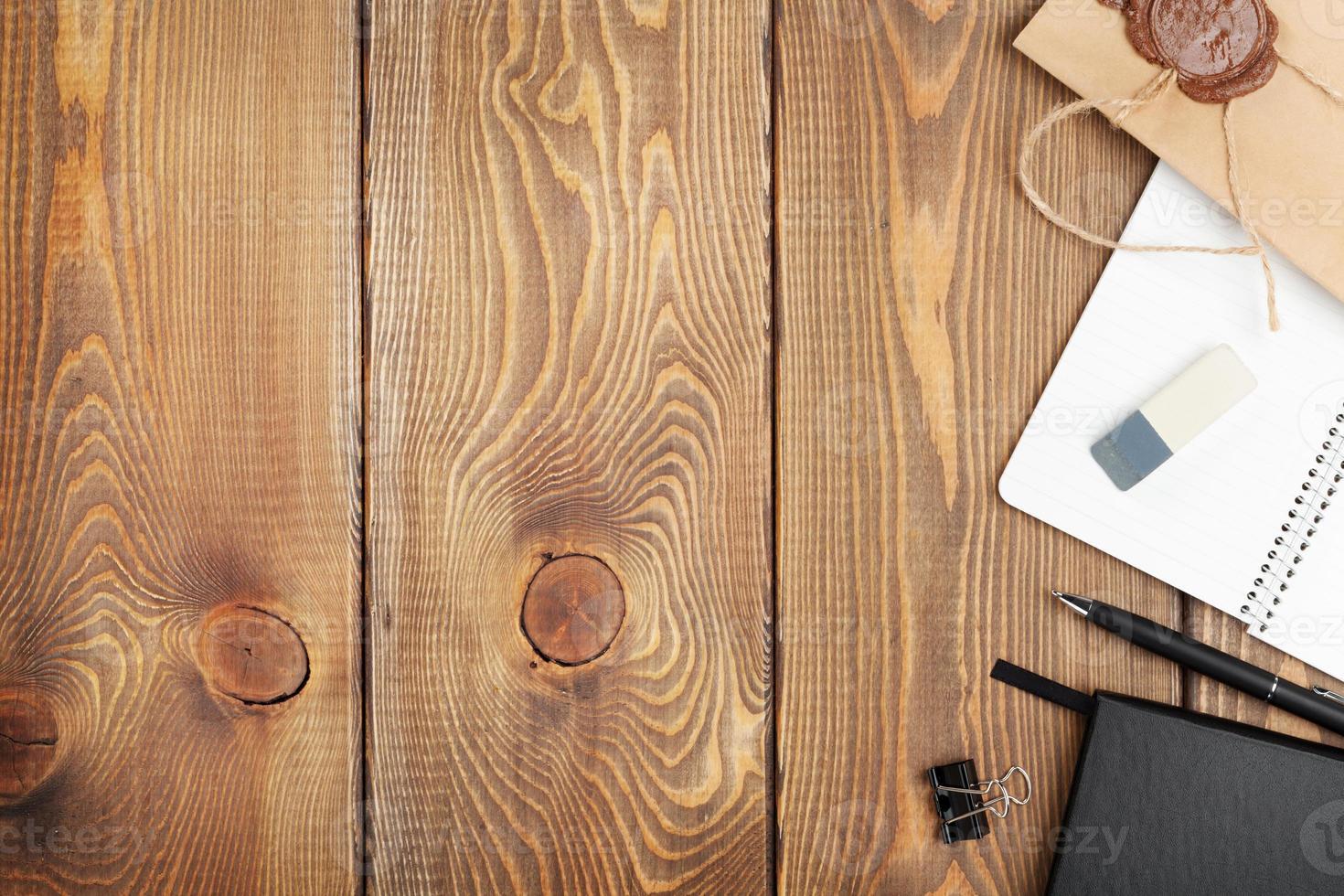 Holztisch mit Notizblock und Vintage-Umschlag foto