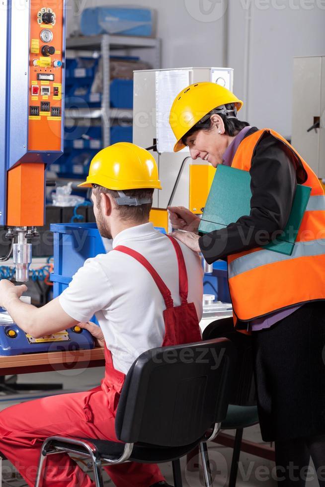 Logistiker, der Arbeiter kontrolliert foto