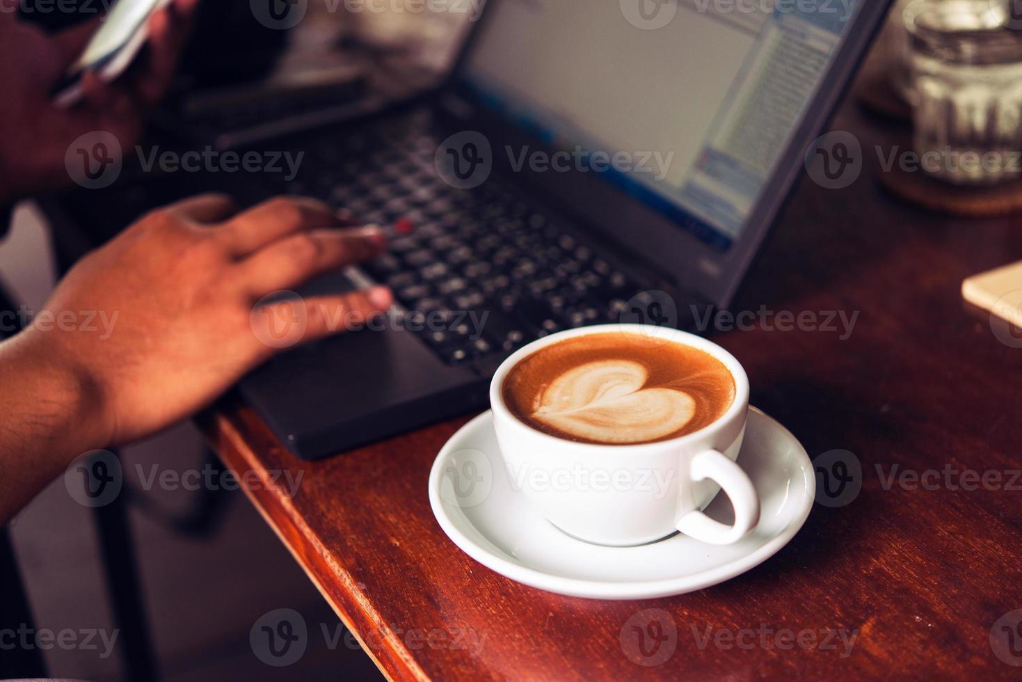 Geschäftsmann arbeitet mit Laptop, hält ein Handy foto