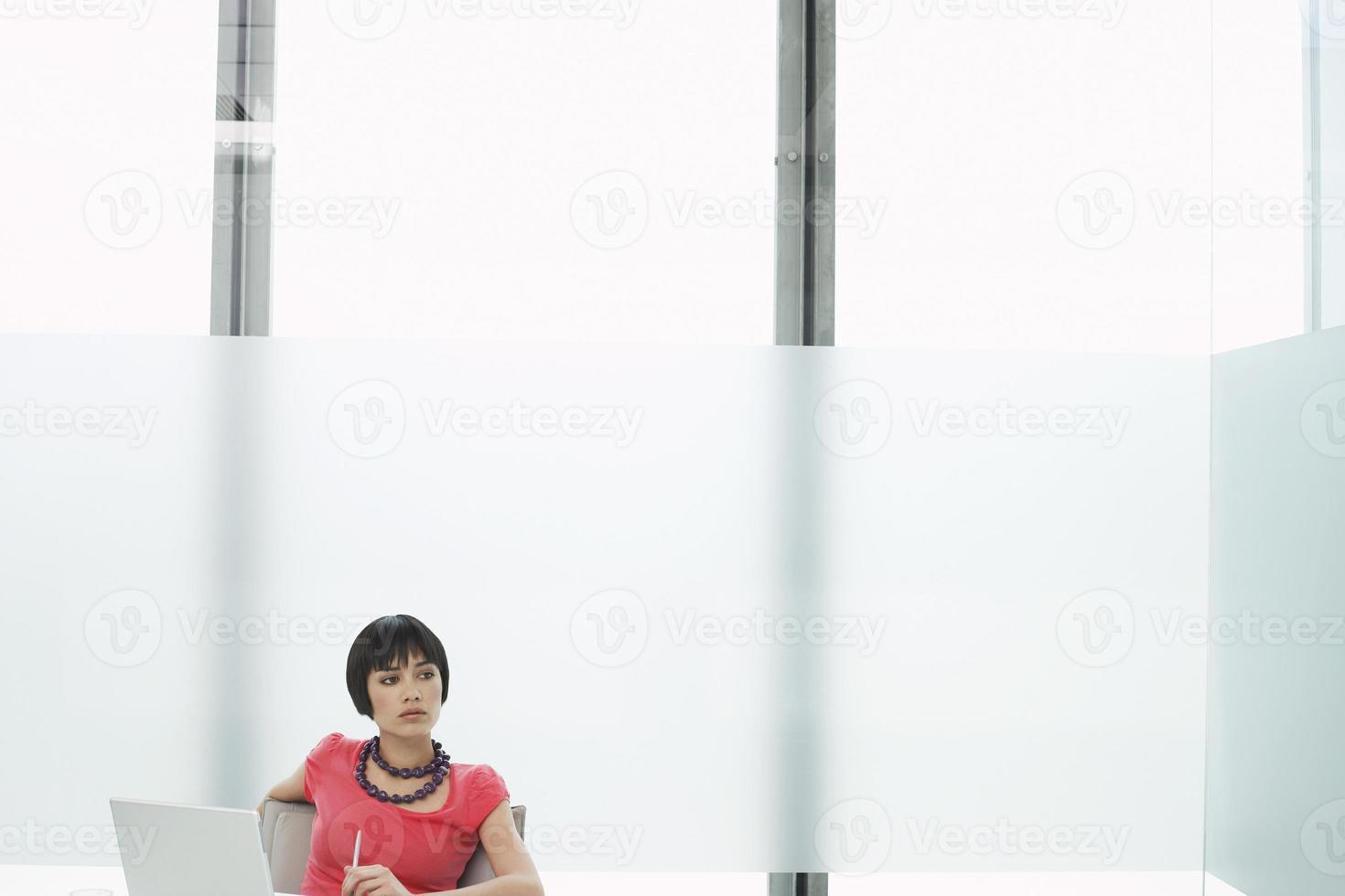 nachdenkliche Frau mit Laptop in der modernen Kabine foto