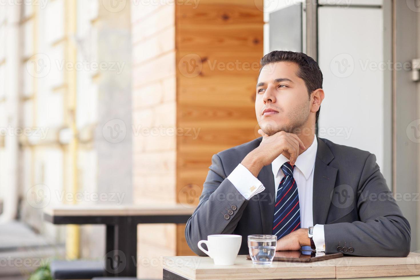Der hübsche männliche Arbeiter ruht sich im Café aus foto