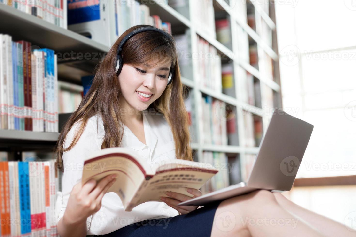 asiatische schöne Studentin, die in Bibliothek mit Laptop studiert foto
