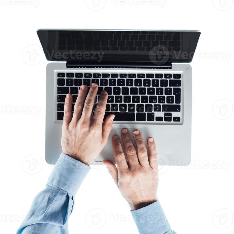 Geschäftsmann, der auf einem Laptop tippt foto