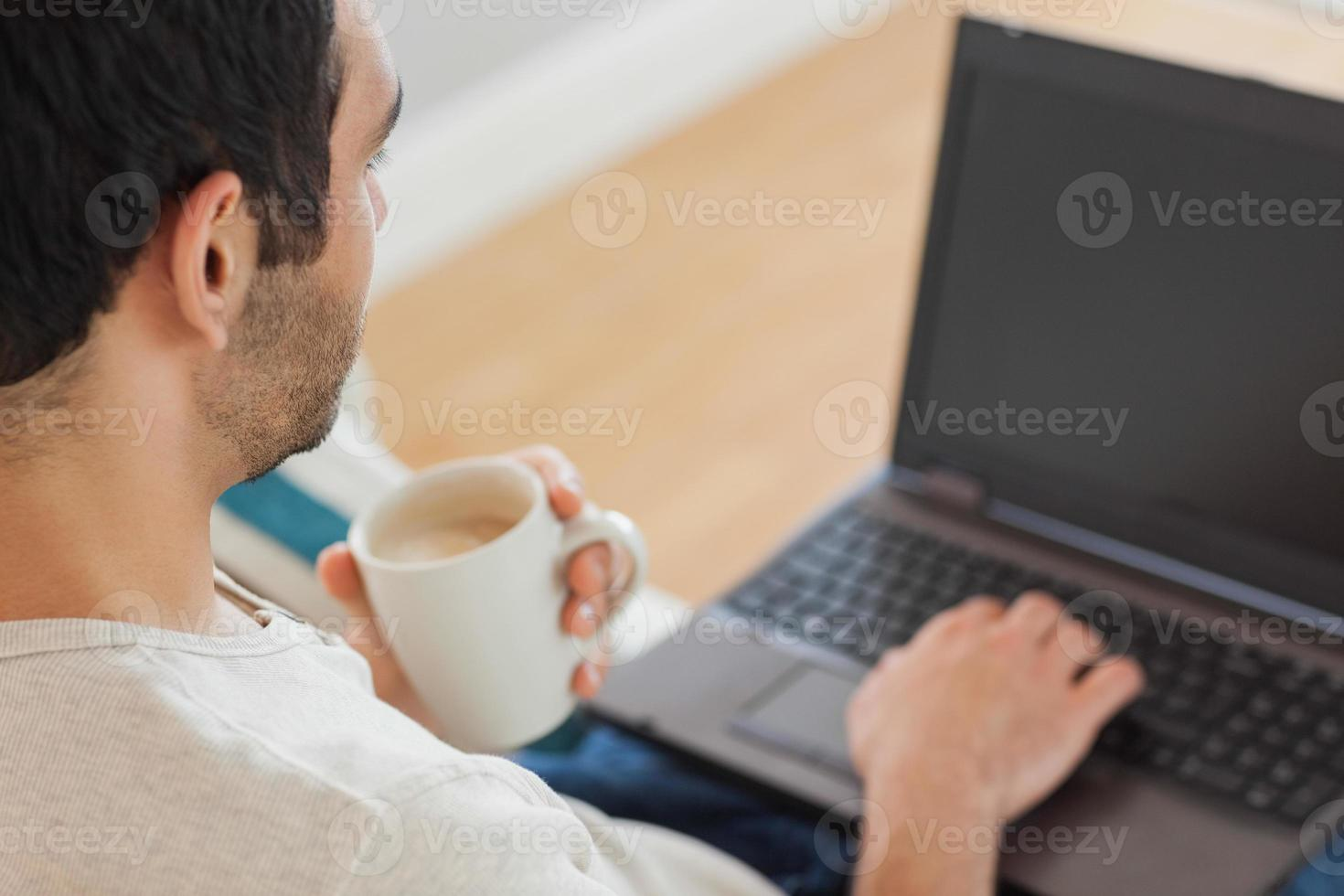 gutaussehender Mann, der Kaffee trinkt, während er seinen Laptop benutzt foto