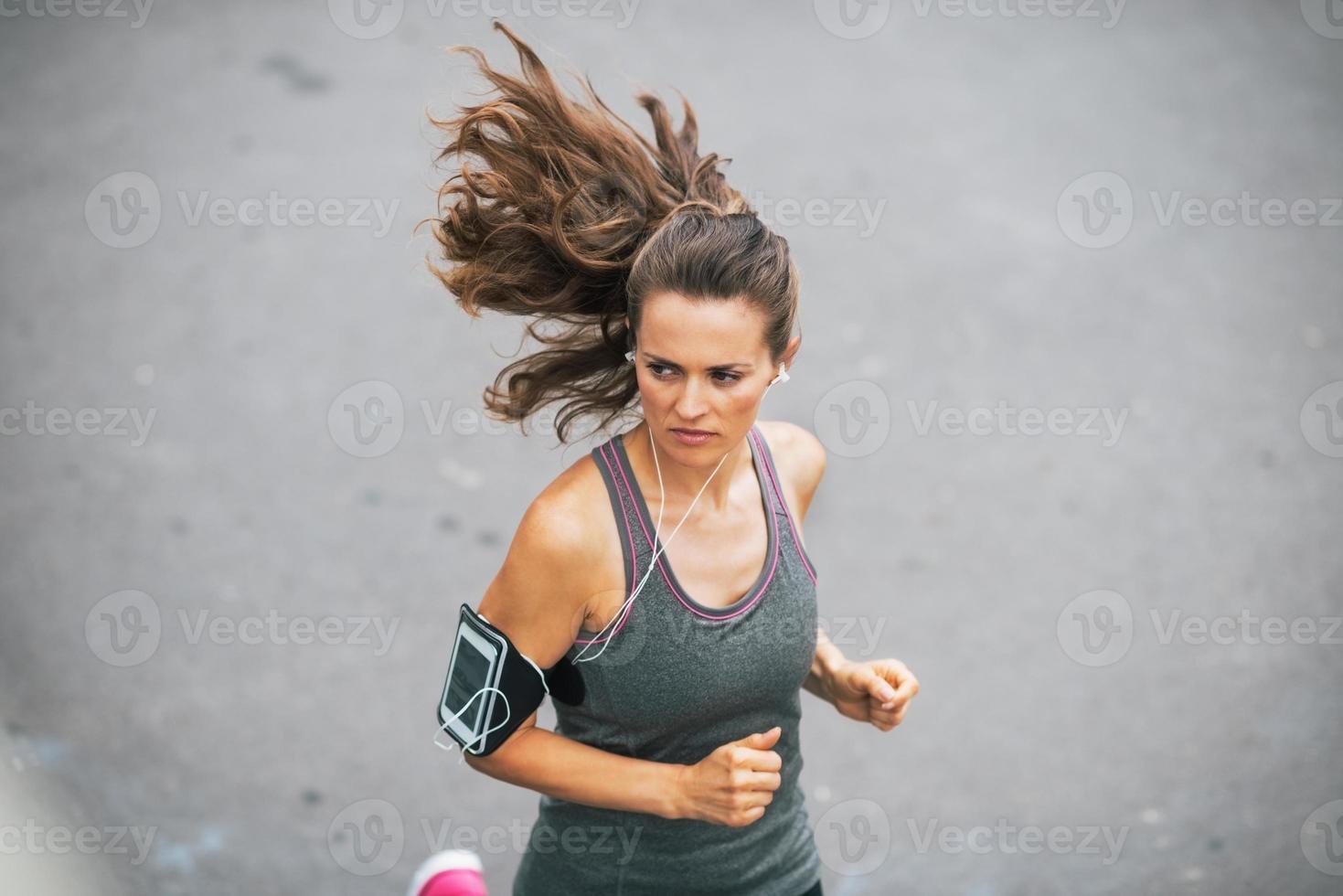 Fitness junge Frau, die draußen in der Stadt joggt foto