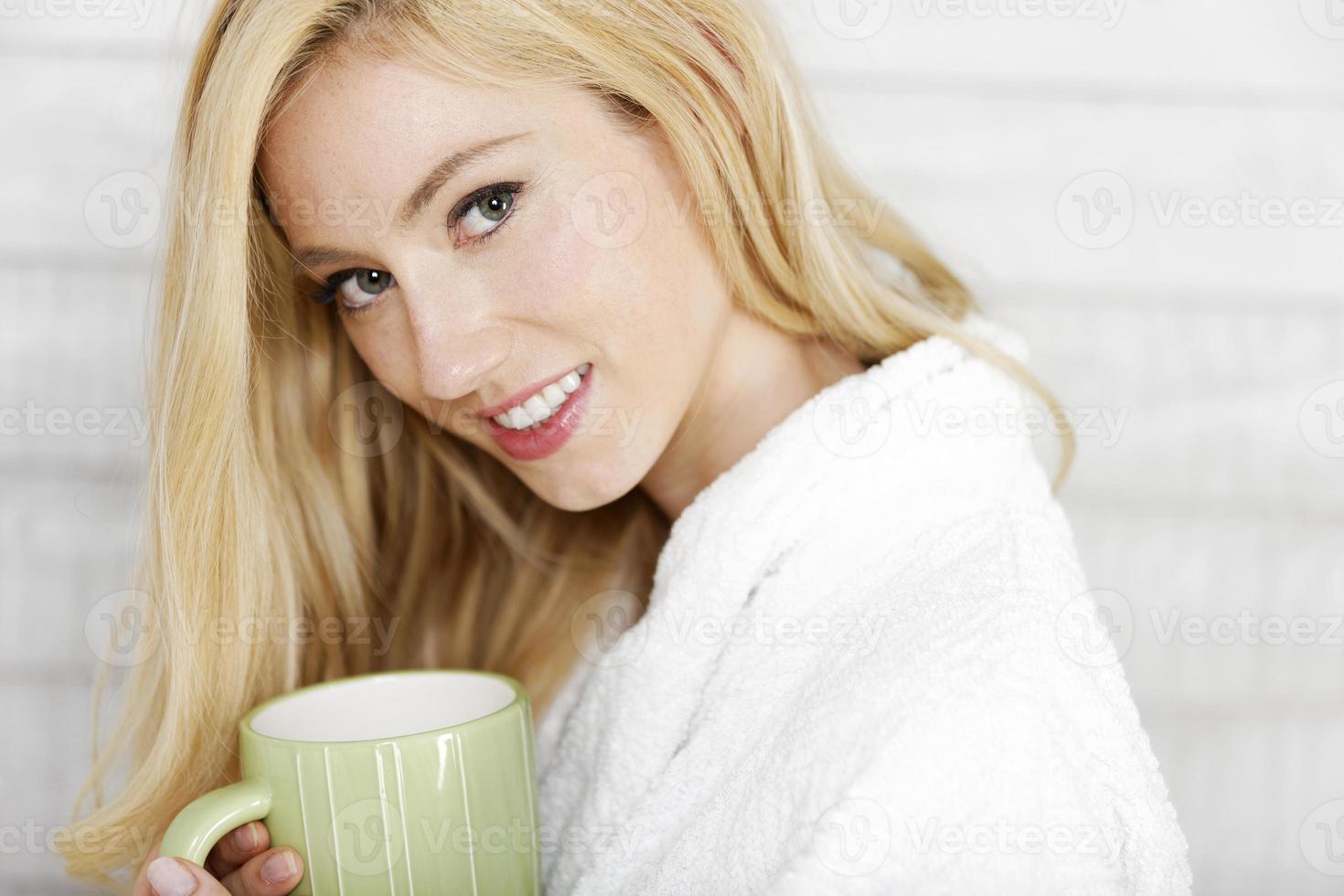 Frau im Gewand genießt heißes Getränk foto