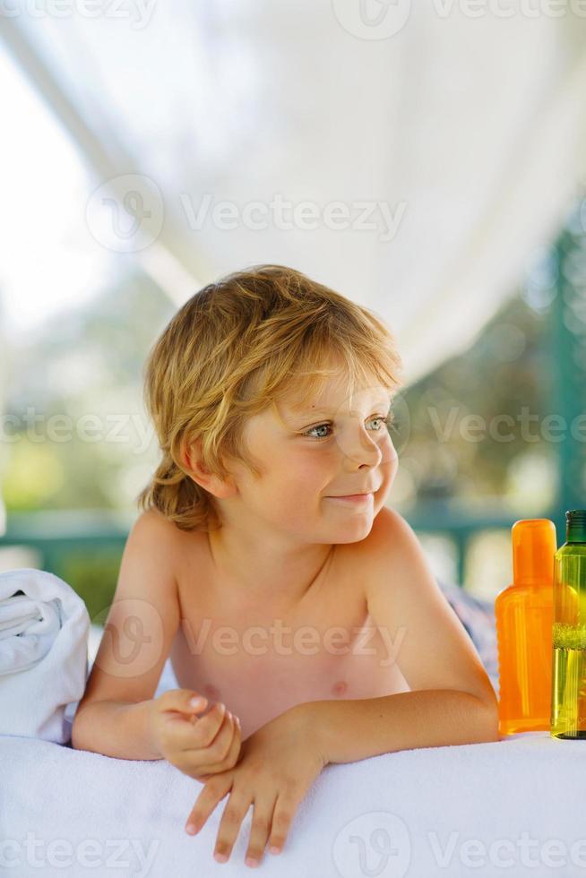 kleiner Junge, der sich im Spa mit Massage entspannt foto