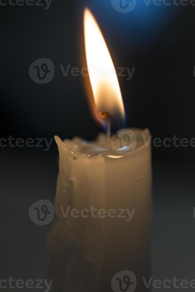 Kerze, die in einem schwarzen Hintergrund glüht foto