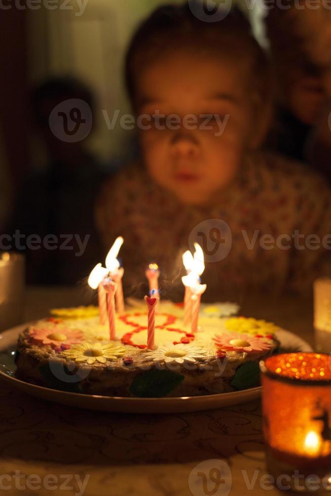 kleines Mädchen, das Kerzen auf Geburtstagstorte ausbläst foto