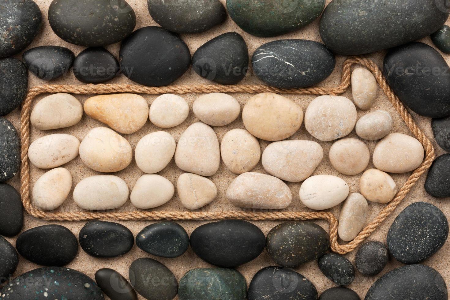 Zeiger aus Seil mit weißen und schwarzen Steinen foto