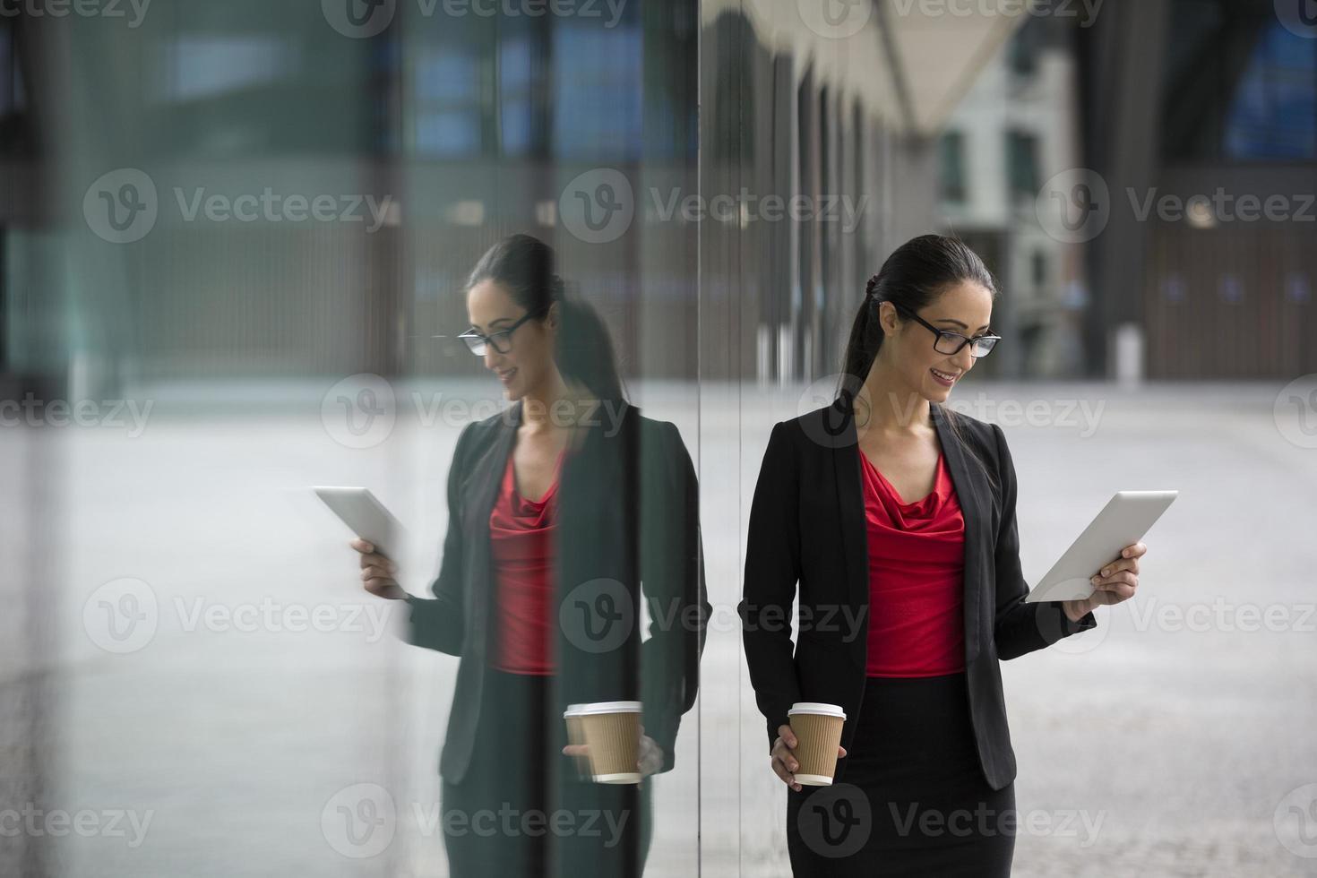 kaukasische Geschäftsfrau, die eine Tablette verwendet foto