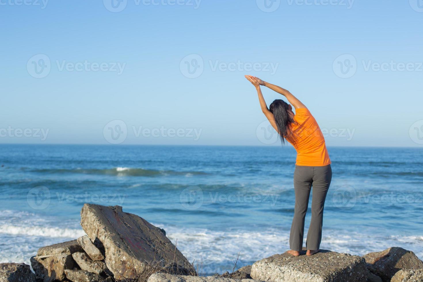 kaukasische Frau, die Yoga an der Küste praktiziert foto