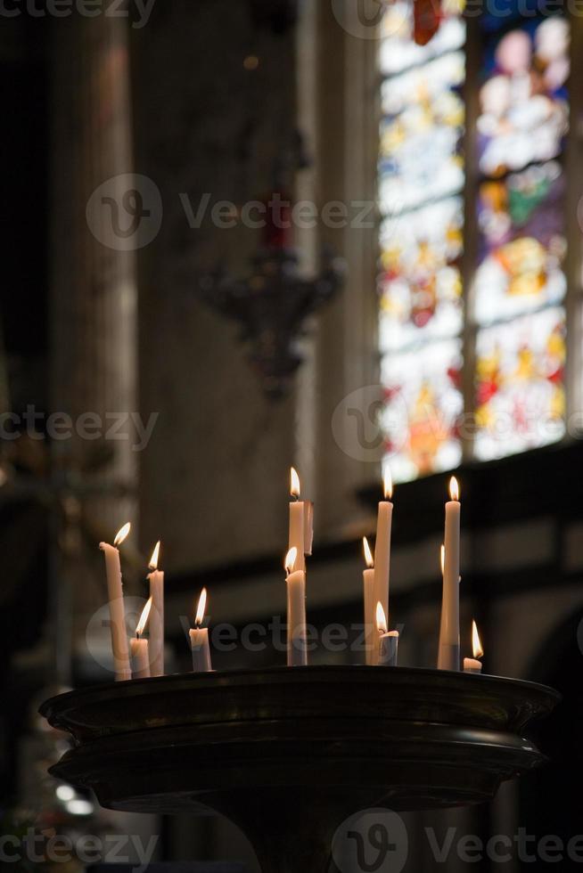 Kirchenkerzen mit Glasmalerei im Hintergrund foto