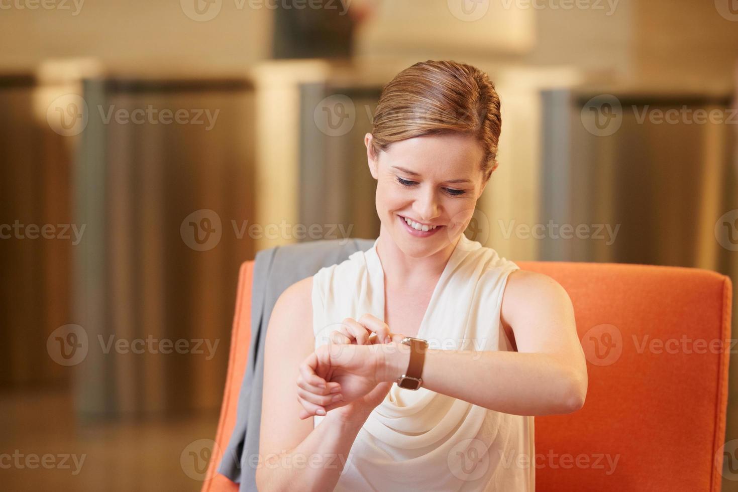 kaukasische Geschäftsfrau, die intelligente Uhr im Geschäftsempfang verwendet foto