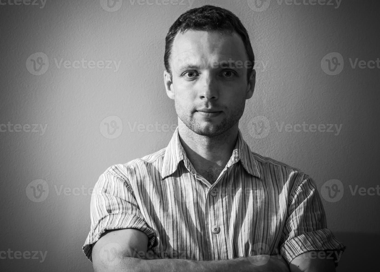 Schwarzweiss-Porträt des jungen kaukasischen Mannes foto