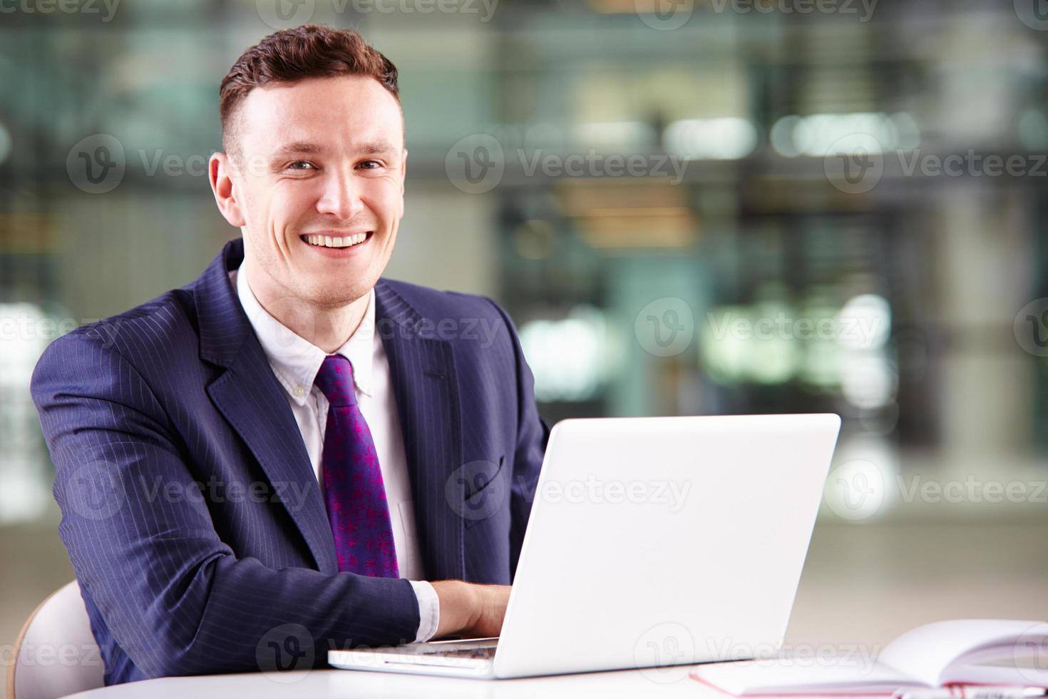 junger kaukasischer Geschäftsmann, der Laptop-Computer bei der Arbeit verwendet foto