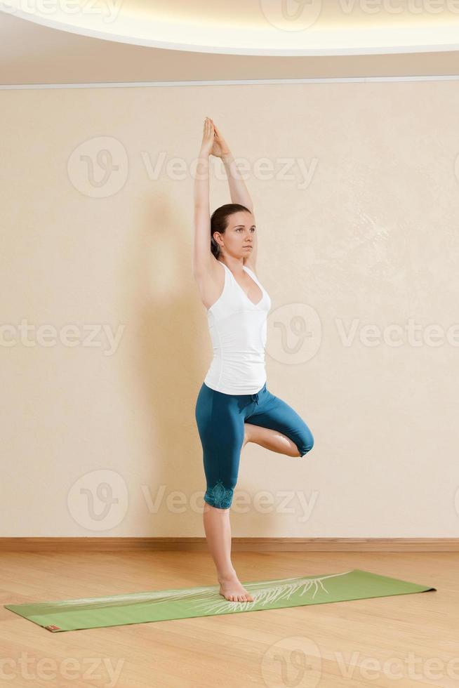 kaukasische Frau praktiziert Yoga im Studio (vrikshasana) foto